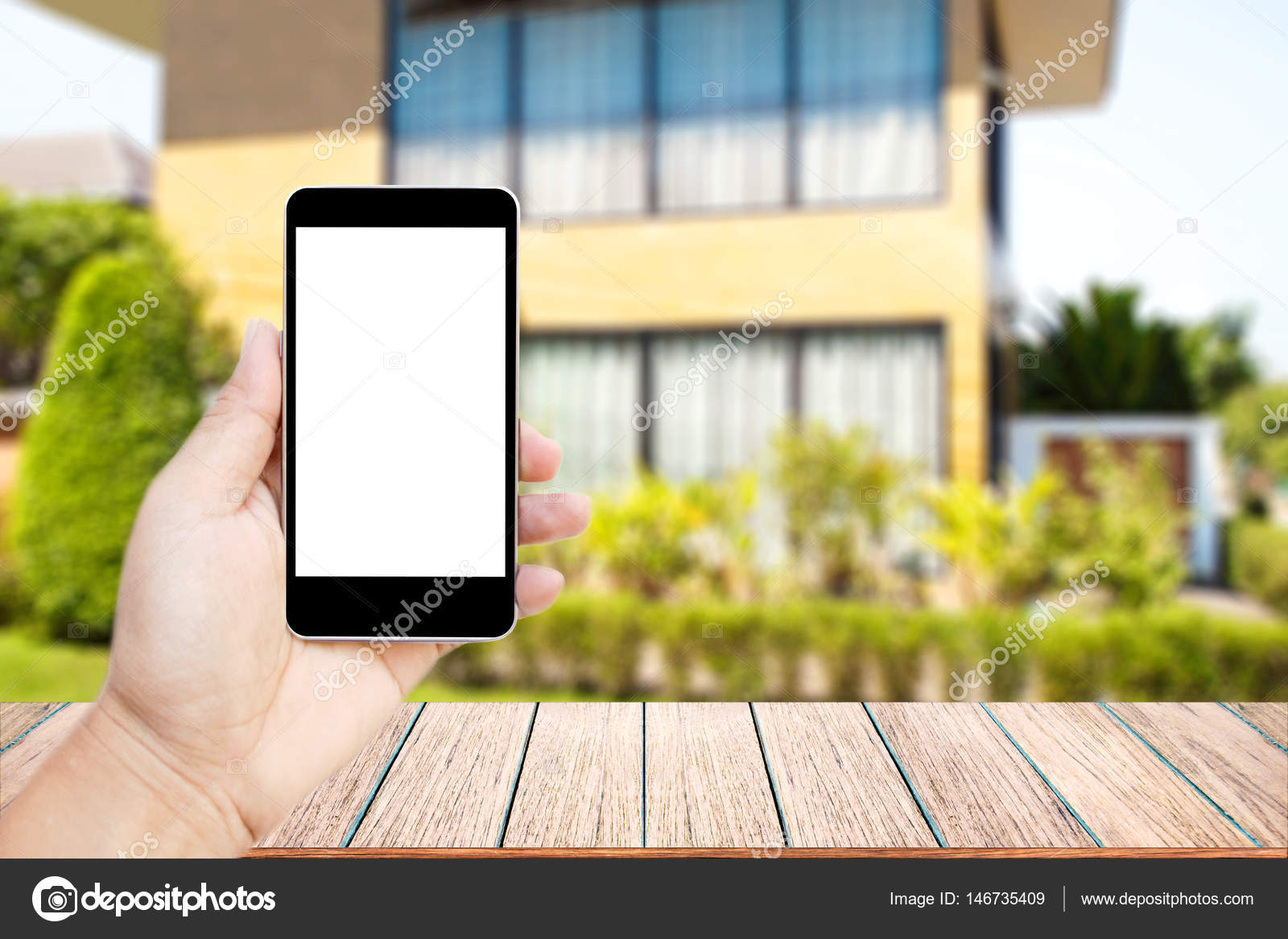 Mock up image of hand holding black mobile phone with blank