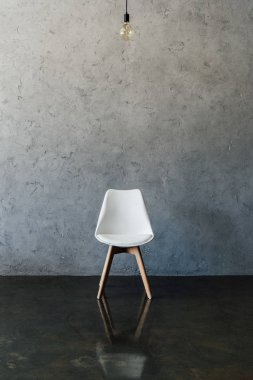 electric bulb and chair at empty room