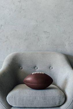 american football ball on grey armchair