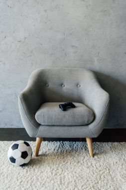 soccer ball near grey armchair with gamepad