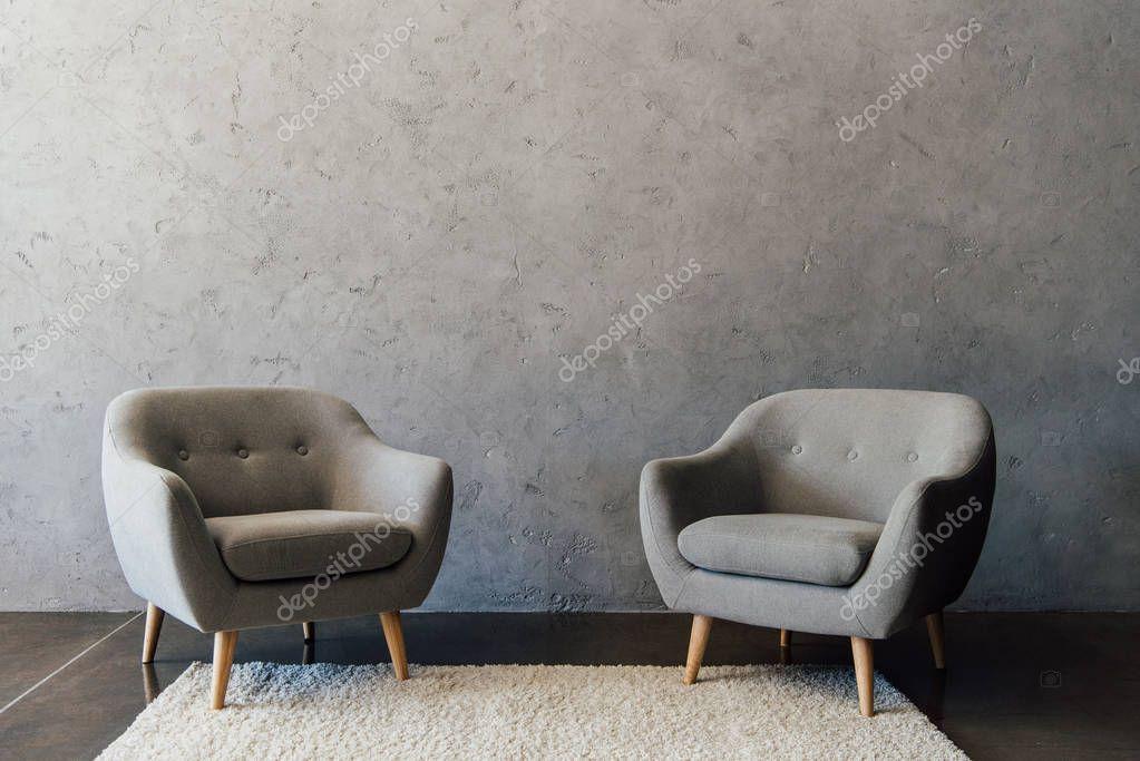 Grey armchairs on carpet