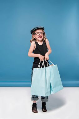 little girl holding shopping bags