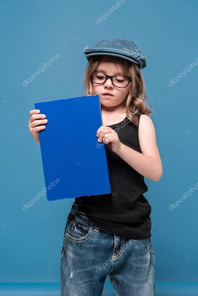 kid girl in glasses holding book