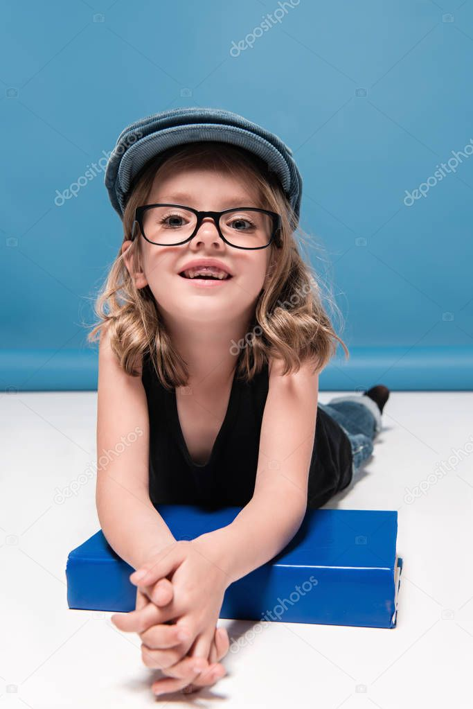 smiling kid girl leaning on book