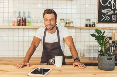 smiling barista at counter with tablet