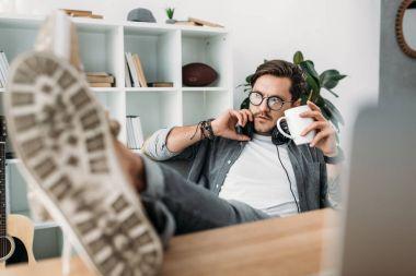 man with headphones drinking coffee