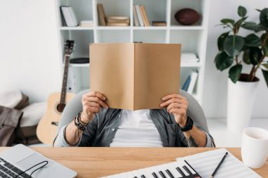 Musician reading magazine with blank cover at workplace stock vector