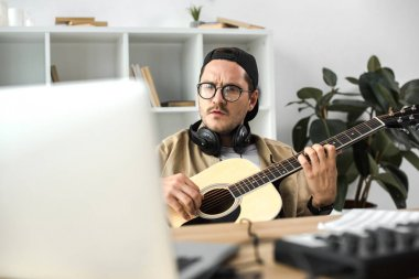 Concentrated man playing acoustic guitar and looking at laptop stock vector
