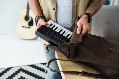 Musician putting MPC pad into bag