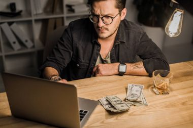 Young man with whiskey and pile of cash using laptop stock vector