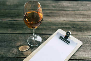 glass of white wine and clipboard