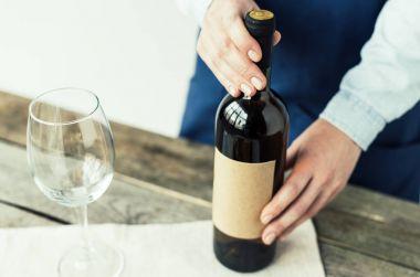 sommelier holding bottle of white wine