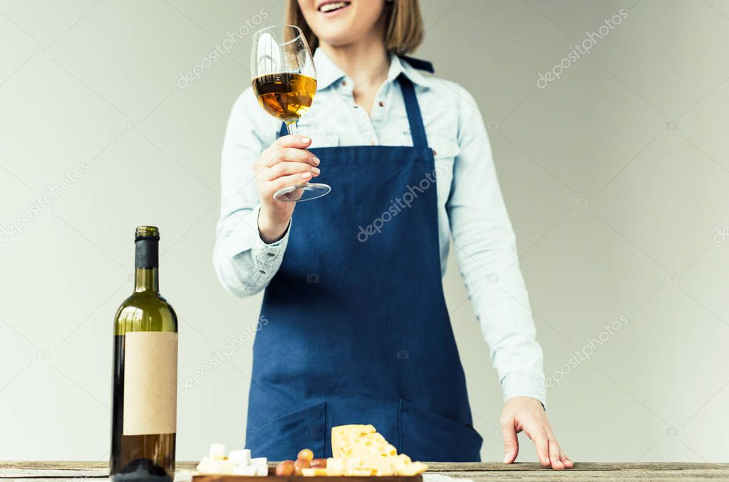 sommelier holding glass of white wine