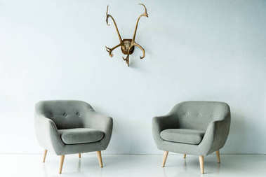 gray armchairs and antlers on wall