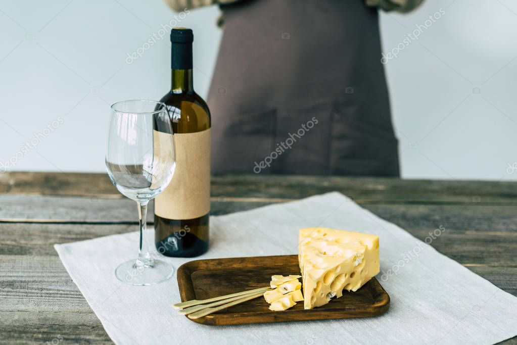 Bottle of wine with empty glass and cheese
