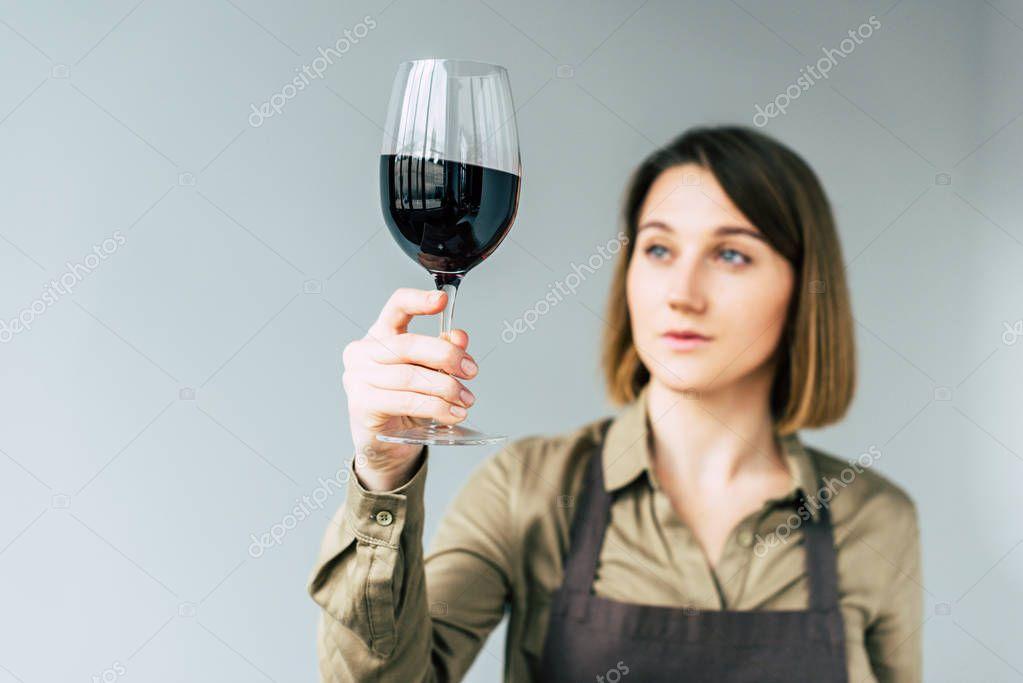 Female sommelier examining red wine