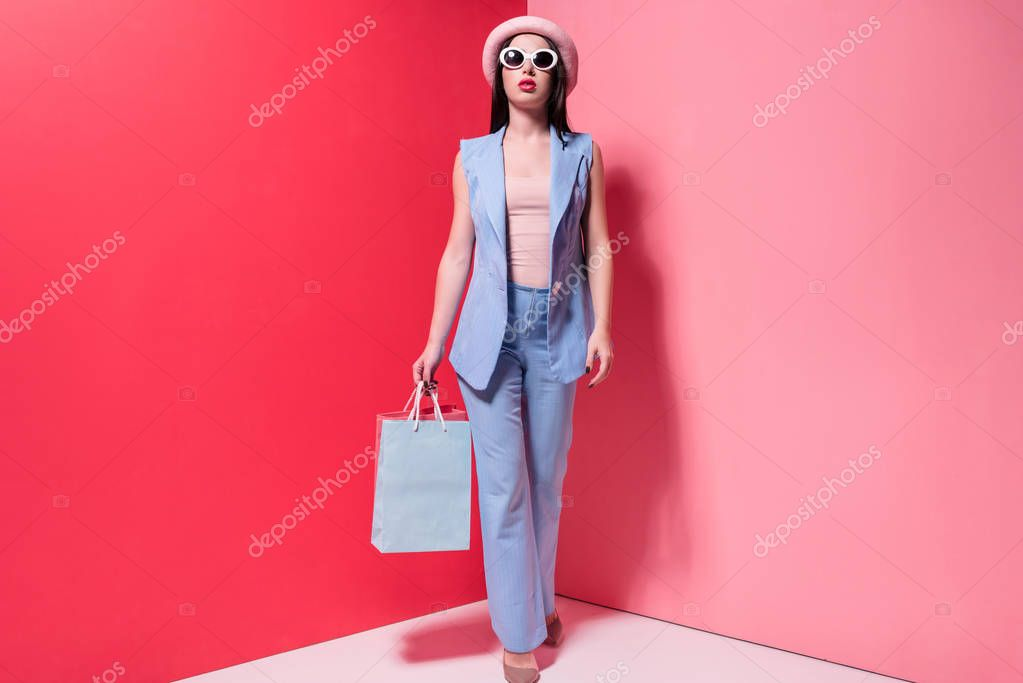 Full length view of stylish young woman in hat and sunglasses holding shopping bags on pink stock vector
