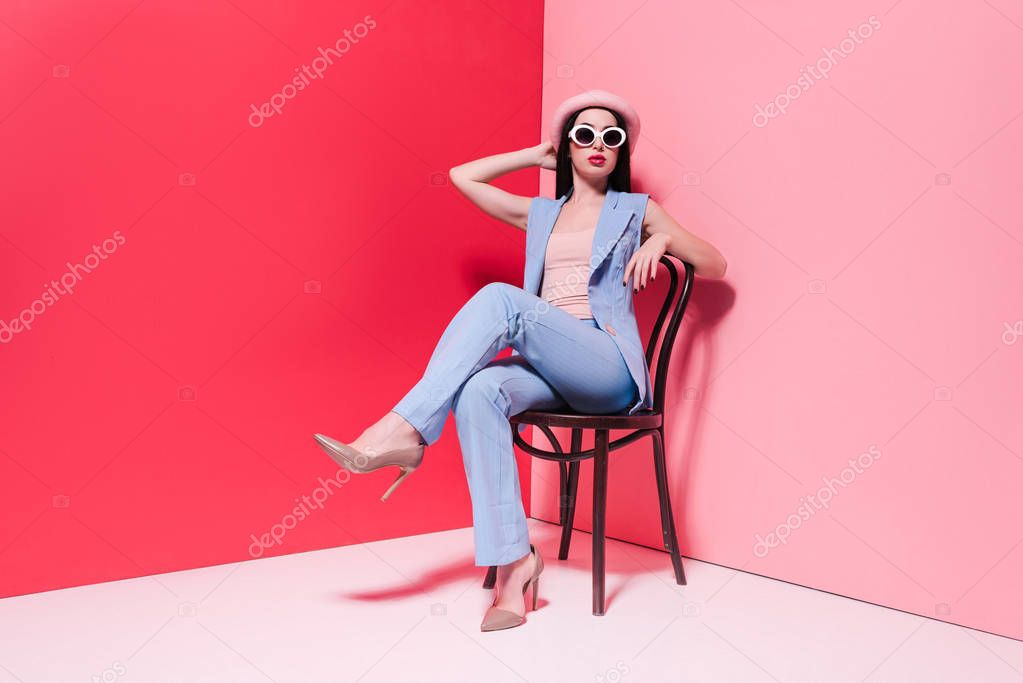 Beautiful stylish girl in hat and sunglasses sitting on chair on pink stock vector