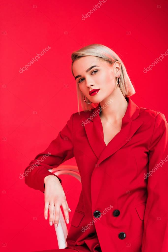 Portrait of blonde stylish girl posing in red jacket, isolated on red stock vector
