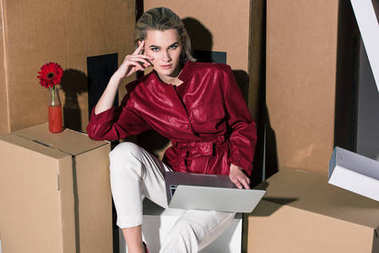 girl with laptop on cardboard boxes