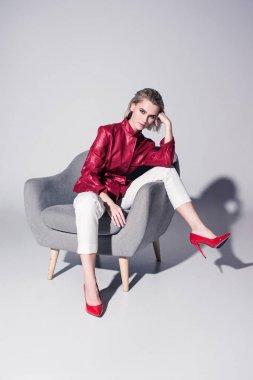 girl posing on armchair for fashion shoot