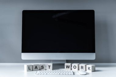 computer and wooden cubes with words Last Work