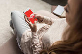cropped shot of woman on couch using smartphone with youtube logo on screen