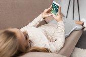 Žena na gauči pomocí chytrého telefonu s ios aplikace na obrazovce