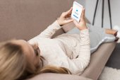 woman on couch using smartphone with messenger app on screen