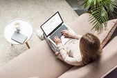 magas szög kilátás nő otthon ül a kanapén, és használ laptop-val google kutatás-ra képernyő