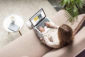 pohled z vysokého úhlu ženy doma sedí na gauči a pomocí přenosného počítače s rezervační stránky na obrazovce