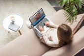 pohled z vysokého úhlu ženy doma sedí na gauči a pomocí přenosného počítače s couchsurfing stránky na obrazovce