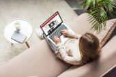 pohled z vysokého úhlu ženy doma sedí na gauči a pomocí přenosného počítače s bbc stránky na obrazovce