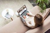 pohled z vysokého úhlu ženy doma sedí na gauči a pomocí přenosného počítače s shutterstock domovskou stránku na obrazovce