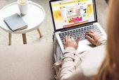 abgeschnittene Aufnahme einer Frau zu Hause, die auf der Couch sitzt und Laptop benutzt, mit aliexpress-Website auf dem Bildschirm