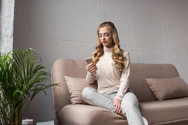 concentrated young woman using smartphone while sitting on couch at home