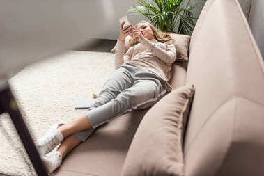stylish young woman using smartphone on cozy couch at home