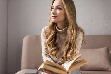 thoughtful young woman with book on cozy couch at home