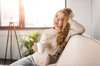 beautiful young woman drinking coffee on couch at home