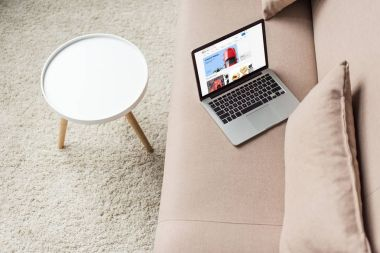 high angle view of laptop standing on cozy couch with ebay website on screen