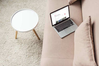 high angle view of laptop standing on cozy couch with airbnb website on screen