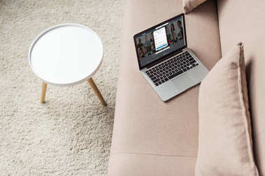 high angle view of laptop standing on cozy couch with linkedin website on screen