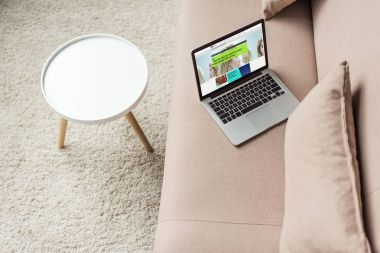 high angle view of laptop standing on cozy couch with bbc website on screen