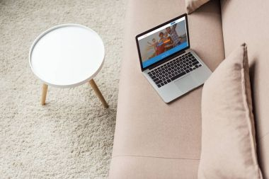 high angle view of laptop standing on cozy couch with couchsurfing website on screen