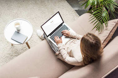 high angle view of woman at home sitting on couch and using laptop with google search on screen