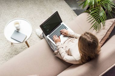 high angle view of young female developer coding with laptop on couch