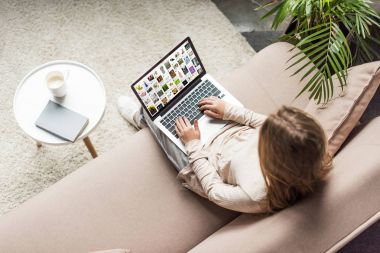 high angle view of woman at home sitting on couch and using laptop with pinterest on screen