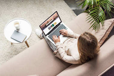 high angle view of woman at home sitting on couch and using laptop with shutterstock website on screen