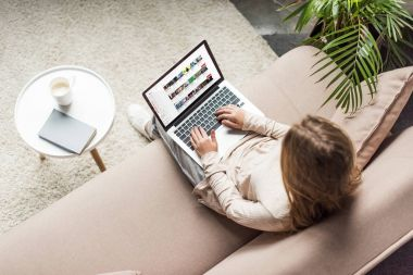 high angle view of woman at home sitting on couch and using laptop with youtube website on screen