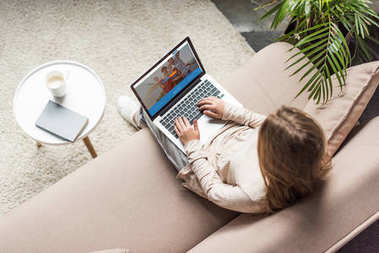 high angle view of woman at home sitting on couch and using laptop with couchsurfing website on screen